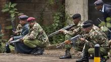 Armed police from the General Service Unit take cover behind a wall during a bout of gunfire, outside the Westgate Mall in Nairobi, Kenya, on Monday, Sept. 23, 2013. (Ben Curtis/Associated Press)