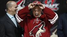 Max Domi tries on a Phoenix Coyotes jersey and cap with team executives after being selected by the Coyotes as the 12th overall pick in the 2013 National Hockey league (NHL) draft in Newark, New Jersey, June 30, 2013. (BRENDAN MCDERMID/REUTERS)