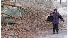A pedestrian makes her way past downed trees as an ice storm ripped through Montreal on Jan. 6, 1998. The storm left over 600,000 people without electricity as ice-covered trees crashed down on power lines. (Ryan Remiorz/The Canadian Press)