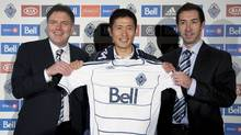 Newly-signed Vancouver Whitecaps FC player Young-Pyo Lee, centre, poses for a photo with team head coach Martin Rennie, right, and team president Bob Lenarduzzi news conference at B.C. Place in Vancouver, B.C. Sunday, Dec, 7, 2011. The team announced Wednesday that they had signed Lee of South Korea to the team. (JONATHAN HAYWARD/THE CANADIAN PRESS)