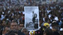 A mourner carries a picture of Fidel Castro before paying tribute to the dead dictator at Revolution Square in Havana on Nov. 29, 2016. (CARLOS BARRIA/REUTERS)