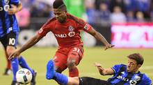 Toronto FC midfielder Armando Cooper (31) battles with the Montreal Impact's Hernan Bernardello during first half action in the first leg of the MLS Eastern Conference final at Olympic Stadium in Montreal on Tuesday. (Ryan Remiorz/THE CANADIAN PRESS)
