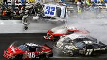Kyle Larson (32) goes airborne into the catch fence in a multi-car crash including Dale Earnhardt Jr. (88), Parker Kligerman (77), Justin Allgaier (31) and Brian Scott (2) during the final lap of the NASCAR Nationwide Series auto race at Daytona International Speedway, Saturday, Feb. 23, 2013. (John Raoux/AP Photo)