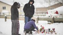 Mourners light candles and place teddy bears with red roses Saturday at the site of the school shooting tragedy in La Loche, Sask., on Friday, Jan. 22, 2016. (John Lehmann/The Globe and Mail)