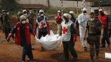 Local Red Cross workers carry a body as they move bodies from a mass grave at a military camp in the 200 villas neighbourhood of Bangui February 17, 2014. (LUC GNAGO/REUTERS)