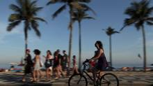 A woman rides a bicycle along the Ipanema beach in Rio de Janeiro July 22, 2012. (Pilar Olivares/REUTERS)
