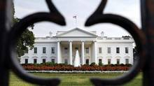 The White House is seen through the fence as debt talks continue in Washington, on Sunday, July 24, 2011. (Jacquelyn Martin/Associated Press)