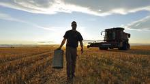 A farm worker carries equipment during the wheat harvest near Fort MacLeod, Alta., on Sept. 26, 2011. (TODD KOROL/REUTERS)