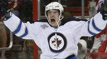 Winnipeg Jets Spencer Machacek (L) celebrates his game-tying goal with teammate Zach Bogosian against the Washington Capitals during the third period of their NHL hockey game in Washington March 23, 2012. REUTERS/Gary Cameron (Gary Cameron/Reuters)