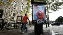 A pedestrian walks past a billboard posted on Mont-Royal Street in the Plateau section of Montreal (Christinne Muschi/Christinne Muschi/The Globe and Mail)