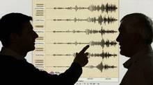 Seismologists examine the graph of a massive arthquake in Japan at the British Geological Survey office in Edinburgh on March 11, 2011. (DAVID MOIR/REUTERS)