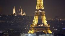The Eiffel Tower is seen at night in front of the Sacre Coeur Basilica on Montmartre, left, in Paris, France (CHARLES PLATIAU/REUTERS)