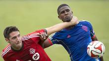 Toronto FC's defender Bradley Orr (left) and and Colorado Rapids forward Edson Buddle (right) battle for the ball during first half MLS action in Toronto on Saturday April 12, 2014. (Frank Gunn/THE CANADIAN PRESS)