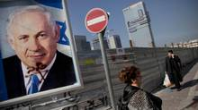 Israelis walk past an election campaign billboard of Israeli Prime Minister Benjamin Netanyahu, in Givataim, Israel, on Sunday, Jan. 20, 2013. (Oded Balilty/AP)