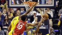Toronto Raptors guard DeMar DeRozan hits a basket between Indiana Pacers center Kevin Seraphin and forward CJ Miles during the second half of an NBA basketball game in Indianapolis, on April 4, 2017. (Michael Conroy/AP)