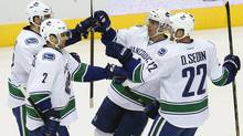 Vancouver Canucks' Ryan Kesler, far left, celebrates his goal against the Phoenix Coyotes with teammates Dan Hamhuis (2), Daniel Sedin (22), of Sweden, and Ryan Kesler during the second period of an NHL hockey game on Tuesday, Nov. 5, 2013, in Glendale, Ariz. (Associated Press)