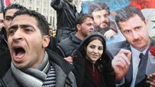 Syrians shout slogans in support of President Bashar al-Assad's regime (portrait-R) during a rally in central Damascus on November 16, 2011 against the latest decision by the Arab League to suspend Syria's membership in the 22-nation Arab body. (LOUAI BESHARA/AFP/Getty Images)