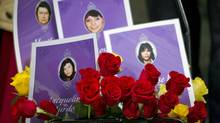 Photos of some of the missing women who were killed by Robert Pickton and the subject of the Missing Women Commission of Inquiry are framed by roses in Vancouver on Dec. 17, 2012. (John Lehmann/The Globe and Mail)