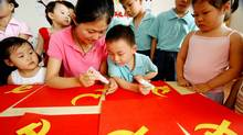 A teacher demonstrates how to make a cut-out of Chinese Communist Party flag at a kindergarten in Lianyungang, in east China's Jiangsu province.