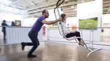 """Nicolas Laverdière aka """"L"""" pushes a guest on Canada de Fantaisie / Canada Fancy, a working carousel by BGL for the Art Toronto show. (Chris Young for The Globe and Mail)"""