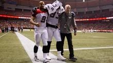 Calgary Stampeders' Micah Johnson, centre, is helped to the locker room by Jon Cornish, left, and Dr. Ian Auld after suffering an injury during first half CFL action against the B.C. Lions in Vancouver, B.C., on Friday November 1, 2013. (DARRYL DYCK/THE CANADIAN PRESS)