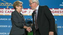 Ontario Premier Kathleen Wynne (left) and Manitoba Premier Greg Selinger shake hands after a moderated discussion at the opening of the Building Canada Up Summit in Toronto on Wednesday August 6, 2014. (Chris Young/THE CANADIAN PRESS)