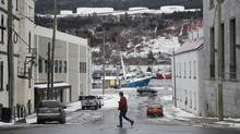A pedestrian walks along Water Street in St. John's, N.L. (Darren Calabrese for The Globe and Mail)