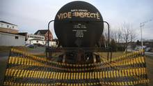 Canadian and U.S. regulators are rushing to update their safety regulations in the wake of several tanker accidents, like the one in Lac-Megantic, where this tanker is cordoned off with an inscription reading, 'empty and inspected,' in 2013. (MATHIEU BELANGER/REUTERS)