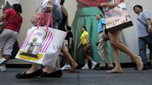 In this July 5, 2011 file photo, pedestrians carrying shopping bags make their way along Fifth Avenue in New York. (Seth Wenig/The Associated Press)