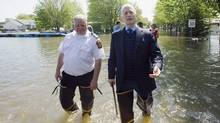 NDP leader Jack Layton, right, takes a walk along a street immersed in flood waters alongside St-Paul fire chief Gilles Bastien in the town of St-Paul-de-I'lle-aux-Noix, Que., Monday, May 30, 2011. (Graham Hughes/The Canadian Press)