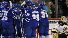 Toronto Maple Leafs players celebrate their overtime win beside Boston Bruins goalie Tim Thomas (R) during the overtime period of their NHL hockey game in Toronto March 9, 2010. REUTERS/ Mike Cassese (MIKE CASSESE)