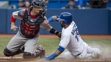 The Toronto Blue Jays Jose Bautista, right, slides past Boston Red Sox catcher Christian Vazquez, left, at home plate to score a run in the first inning during their game in Toronto on Wednesday. (Nathan Denette/THE CANADIAN PRESS)