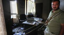A rebel stands guard at the ruined offices of Libya's foreign intelligence service in Tripoli. Rebels at that office said that NATO has instructed them to avoid letting anybody read the papers scattered inside. Elsewhere in the city, however, The Globe and Mail searched through stacks of documents, some of which chronicle the efforts of security officers to save Col. Gadhafi's regime during its final months. (Graeme Smith/The Globe and Mail/Graeme Smith/The Globe and Mail)
