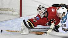 Calgary Flames' Miikka Kiprusoff makes a dive against San Jose Sharks' James Sheppard during the first period of their NHL game in Calgary, Alberta, March 6, 2013. (STRINGER/CANADA/REUTERS)