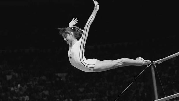 "Nadia Comaneci dismounts from the uneven parallel bars during a perfect ""10"" performance at the Summer Olympic Games in Montreal, in this July 18, 1976 photo (Associated Press)"