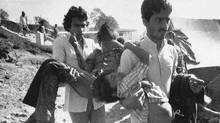 In this Dec. 5, 1984 file photo, two men carry children blinded by the Union Carbide chemical pesticide leak to a hospital in Bhopal, India. The tragedy left an estimated 15,000 people dead. AP Photo/Sondeep Shankar, File (Sondeep Shankar/AP)