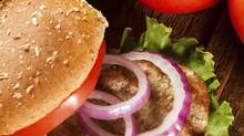 Turkey burgers deliver far less fat and few calories than beef. Cocktails without the sugar and kebabs instead of ribs can help minimize waistline barbecue damage. (Getty Images/iStockphoto)
