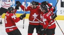 Switzerland's players celebrate their fourth goal against Canada Wednesday in Mannheim. (PETR JOSEK)