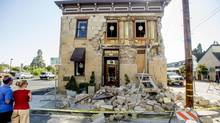 Pedestrians stop to examine a crumbling facade at the Vintner's Collective tasting room in Napa, Calif., following an earthquake Sunday, Aug. 24, 2014. (Noah Berger/AP)