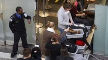 A U.S. Transportation Security Administraion (TSA) employee (L) watches on as airline passengers empty the contents of their pockets and bags onto trays at a security chekckpoint at Washington Reagan National Airport January 4, 2010. (JASON REED)
