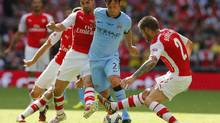 Manchester City's David Silva is tackled by Arsenal's Mikel Arteta and Mathieu Debuchy (SUZANNE PLUNKETT/REUTERS)