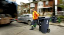 Jimmy McIsaac picks up garbage and recyclables on his route on Grace Street, north of Harbord Street, in Toronto. He's worked for the city for 11 seasons, five with the sanitation department. (Peter Power/The Globe and Mail/Peter Power/The Globe and Mail)