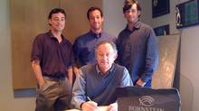 Kyle, Colin and Andrew Bornstein witness father Jay Bornstein as he signs a Memorandum of Understanding confirming his agreement to sell Bornstein Seafoods to his three sons, who will be equal partners.
