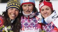Norway's gold medal winner Marit Bjoergen is flanked by Sweden's silver medal winner Charlotte Kalla, left, and Norway's bronze medal winner Heidi Weng after the flower ceremony for the women's cross-country 15k skiathlon at the 2014 Winter Olympics, Saturday, Feb. 8, 2014, in Krasnaya Polyana, Russia. (Dmitry Lovetsky/AP)