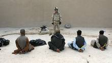 A member of Reconnaissance Platoon, 1st Princess Patricia's Canadian Light Infantry, guards six of ten suspected Taliban prisoners captured in a raid on a compound in Northern Kandahar, in this May, 2006 file photo. (JOHN D MCHUGH)