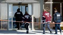 Police officers and paramedics arrive at the scene at the Châteauneuf Hotel in Laval, Que., Wednesday, January 18, 2012 where former Montreal police Sgt. Ian Davidson, who allegedly tried to sell a list of police informants to the Mafia, was found dead. (Graham Hughes/Graham Hughes/The Canadian Press)