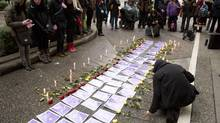 Photos and roses are place on the ground as part of a memorial to missing women in Vancouver before the report from the Missing Women Commission of Inquiry is released. (John Lehmann/The Globe and Mail)
