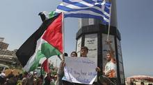 Palestinians hold flags during a rally in support of a Gaza-bound flotilla, at the Gaza seaport July 3, 2011. (MOHAMMED SALEM/REUTERS)