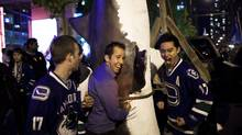 Vancouver fans celebrate by beating on a fake shark hanging from a truck at CBC plaza after the Vancouver Canucks won Game 5 and the series against the San Jose Sharks. (Rafal Gerszak for The Globe and Mail)