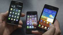 A man holds a Samsung S II, right, and Samsung Ace. left, smartphones next to an Apple iPhone 4 in this photo illustration August 24, 2011. The Galaxy S II features a larger screen than the iPhone. (MICHAEL KOOREN/Michael Kooren/REUTERS)